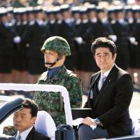 Present arms: Prime Minister Shinzo Abe reviews Self-Defense Forces ranks at Camp Asaka, northwest of Tokyo, last October. | AP