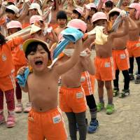 In the pink: Kids towel off after exercising at a playground at Tokyo's Mizuho Kindergarten on Monday, the day on traditional Japanese calendars recognized as 'daikan' (major cold), or the chilliest day of the year. The 500 kindergartners play shirtless every day to stay healthy. | AFP-JIJI