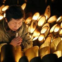Prayers amid the lights: A woman prays for the victims of the 1995 Great Hanshin Earthquake early Friday at a park in Kobe's Chuo Ward, where bamboo lanterns were arranged to mark the 19th anniversary of the killer quake. | KYODO