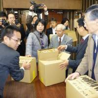 People power: Members of an anti-nuclear citizens' group in Shimane Prefecture submit signatures to the Matsue Election Administration Commission on Monday asking for a prefectural ordinance to phase out atomic power. | KYODO