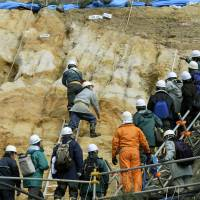 Digging deep: Experts from the Nuclear Regulation Authority examine the soil around reactor 2 at Tsuruga nuclear power plant in Fukui Prefecture on Monday. | KYODO