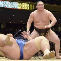 Rough and rugged: Yokozuna Hakuho topples ozeki Kotoshogiku on Saturday at the New Year Grand Sumo Tournament. | KYODO