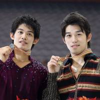 Stellar result: Silver medalist Takahiko Kozuka (left) and gold medalist Takahito Mura display their medals at the Four Continents Championships on Friday in Taipei. | AP