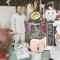 Attention grabbers: Masahide Nakamura, president of Pop Kougei Co., poses with some '3-D ads' his company created at his factory in Yao, Osaka Prefecture, on Dec. 6. | KYODO