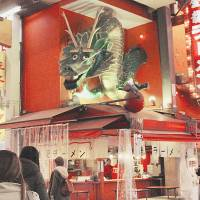 First of its kind: A green dragon sculpture, installed above a ramen shop in Osaka's Dotombori district, is the first so-called 3-D ad Pop Kougei Co. created, in 1997. | KYODO