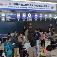 Everyone counts: A signboard marking the arrival of 10 million tourists to Japan is shown in the arrival lobby at Chubu Centrair Japan International Airport, Nagoya on Dec. 25. | CHUNICHI SHIMBUN