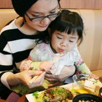 Eating green: A mother and daughter try a hamburger dish containing euglena at a restaurant in Shinagawa Ward, Tokyo, in December. | KYODO