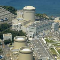 The Mihama nuclear power plant is seen from the air last May in Fukui. Kansai-area governments have their hands tied when it comes to developing a nuclear evacuation plan. | KYODO