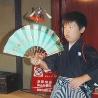 The knack: Chikuzen Hakata Koma artist Kazuma Yoshitomi, 10, spins a top on Sept. 29. He recently assumed the name of Chikushi Juraku as the successor to a long line of spinning top performers. | KYODO