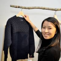 Made to order: Tamako Mitarai, CEO of Kesennuma Knitting Co., shows off one of her company's products on Nov. 29 in Tokyo's Omotesando district. | YOSHIAKI MIURA