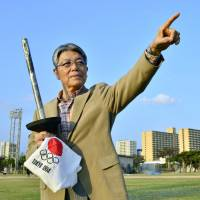 Carried the flame: Isamu Miyagi, the first Japanese torchbearer for the 1964 Tokyo Olympics, stands with the torch and his uniform in an athletic field in Naha, Okinawa Prefecture, in December. | KYODO