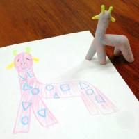 Proud papa: A plaster giraffe commissioned by a father stands next to his daughter's drawing that served as the blueprint for a 3-D printer in Osaka in November. | KYODO