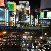 Lighting the way: Cars travel along Ome Kaido Avenue in Shinjuku at twilight. | SATOKO KAWASAKI