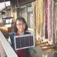 The power of one: Chikako Fujii, known online as the 'solar joshi' (solar girl), poses with a solar panel she installed at her home in Kunitachi, western Tokyo, to produce her own electricity. The anti-nuclear campaigner's electricity bill is now around ¥400 a month. | TOMOHIRO OSAKI