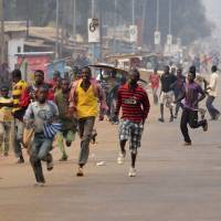 Quick exit: Looters run for cover after hearing rifle shots near the 'Reconciliation Crossroad' in Bangui on Saturday. | AFP-JIJI