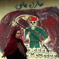 Not to be trifled with: A woman walks past graffiti depicting Egypt's security apparatus in Cairo in May 2012. | AFP-JIJI