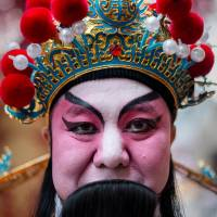 Dressed for success: A performer dons traditional garb Jan. 23 ahead of the Chinese New Year in Hong Kong on Friday. | AFP-JIJI