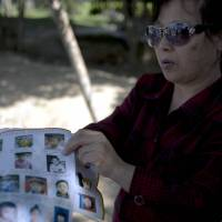 Living in hope: Ye Jinxiu displays pictures of missing children on a street in Fuzhou, in the east coast province of Fujian, on Oct. 23. Ye is helping other parents search for their children. | AFP-JIJI