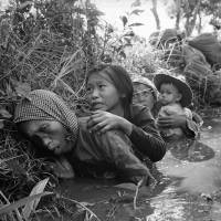 Sitting ducks: Women and children crouch in a muddy canal as they take cover from intense Viet Cong fire at Bao Trai, about 35 km west of Saigon, in January 1966. It took nearly five years of tortuous negotiations by two U.S. administrations to hammer out the 1973 Paris Peace Accords aimed at ending the Vietnam War. | AP