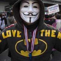 Holy mixed message!: An anti-government protester in a Guy Fawkes mask expresses support for the king in Bangkok on Monday. | AP
