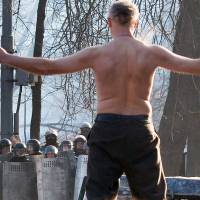 Topless protest: A shirtless man confronts riot police as protesters and authorities clash in Kiev on Monday.  | AFP-JIJI