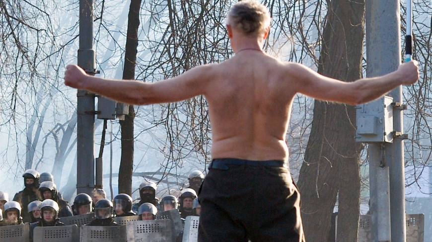 Topless protest: A shirtless man confronts riot police as protesters and authorities clash in Kiev on Monday.