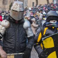 Getting medieval: Protesters clad in improvised protective gear prepare to clash with police in central Kiev on Monday. | AP