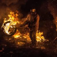 Demonstrators burn tires to warm themselves at a barricade in the capital Friday. | AFP-JIJI