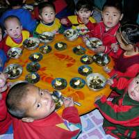 A place at the table: North Korean children eat lunch provided by the U.N. World Food Program at a nursery in Yomju County, North Pyongan province, in February 2005. | AFP-JIJI