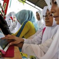 Popular people: Indonesian students share a tablet computer to check their Facebook accounts in Banda Aceh on Dec. 31. | AP