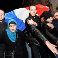 Nazi or not?: People make 'quenelle' salutes in front of a Paris theater where comic Dieudonne M'Bala M'Bala was performing on Dec. 28. They were protesting against a call by Interior Minister Manuel Valls for Dieudonne's new tour performances to be banned. | AFP-JIJI