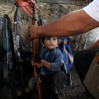 Young recruit: A child tries to help his father arrange weapons at a checkpoint set up by the Self-Defense Council of Michoacan in Tancitaro, Mexico, on Jan. 16. | AP