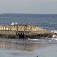 Worn by waves: The remains of a Mulberry harbor stand on the beach of Arromanches-les-Bains, northern France. | AFP-JIJI