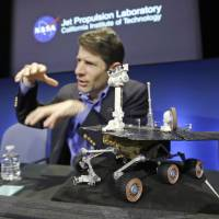 Desert trooper: Mars Exploration Rovers project manager John Callas, with a one-tenth scale model of Opportunity beside him, speaks at a news conference marking the 10th anniversary of the rover's mission on Thursday in Pasadena, California. | AP