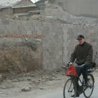 End of an era: A man cycles past the demolished Tianyi Inn in Beijing on Jan. 7. | AFP-JIJI