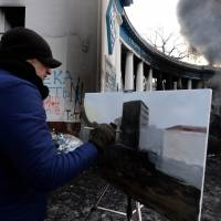 Paint it black: An anti-government protester paints a scene of fellow demonstrators clashing with riot police in central Kiev on Saturday. | AFP-JIJI