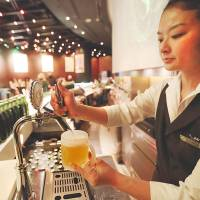 Last call: A bartender pours a glass of Heartland beer in the Heartland bar at the Roppongi Hills complex in Tokyo last April. The bar effectively closed Monday. | BLOOMBERG