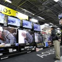 Sharp decline: Customers check out Sharp Corp.'s Aquos televisions at an electronics store in Tokyo last February. | BLOOMBERG