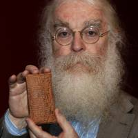 New evidence: Irving Finkel, curator in charge of cuneiform clay tablets at the British Museum in London, holds a 4,000-year-old tablet containing a Babylonian version of the biblical flood story at the launch of his book 'The Ark Before Noah' at the museum on Friday. | AP