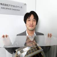 Yuya Nakamura, president and chief executive officer of Axelspace, shows one of the firm's satellites. | BLOOMBERG