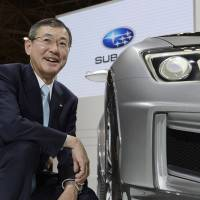 Big winner: Fuji Heavy Industries Ltd. President Yasuyuki Yoshinaga poses next to Subaru's Cross Sport Design Concept vehicle at the Tokyo Motor Show on Nov. 20. | BLOOMBERG