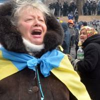 At loggerheads: A Ukrainian opposition activist addresses riot police standing guard outside parliament in Kiev on Tuesday. | AFP-JIJI
