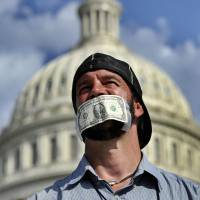 Denied: A man joins a protest in front of the Capitol on Oct. 1 urging Congress to pass the budget bill. | THE GOVERNMENT SHUT DOWN THE SAME DAY.AFP-JIJI