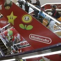 Climbing Koopas: Shoppers take escalators painted with the logo of Nintendo and Super Mario characters at an electronics store in Tokyo in December. | AP