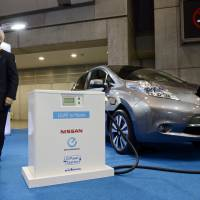 Plugged in: A Nissan Motor Co. Leaf electric vehicle is connected to a charging point at the ITS World Congress Tokyo 2013 transportation trade show on Oct. 15. | BLOOMBERG