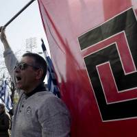 Dark days: Supporters of the Greek ultranationalist Golden Dawn party shout slogans outside a courthouse in Athens on Saturday. | AFP-JIJI