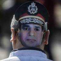 Military might: A supporter of Egyptian Army chief Abdel-Fattah el-Sissi, who is expected to run in the upcoming presidential elections, wears a mask bearing the image of the defense minister during a demonstration outside the in Cairo police academy where the new trial of deposed President Mohammed Morsi opened Tuesday. | AFP-JIJI