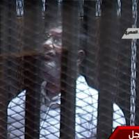 Glass ceiling: Toppled President Mohammed Morsi stands inside a glass-encased metal cage in a Cairo courtroom Tuesday. Morsi was separated from other defendants for the start of a new trial over charges he aided prison breaks during the country's 2011 revolution. | AP