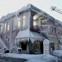 Encased: Sunlight streams through the windows of a building that caught fire in Plattsmouth, Nebraska, on Friday, after the water sprayed on it by firefighters froze. | AP