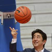 Free throw: Prime Minister Shinzo Abe tosses a basketball after his meeting with members of the Mozambican women's basketball team in Maputo on Sunday. | AFP-JIJI